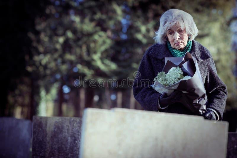 Traurige ältere Frau mit den Blumen, die Grab bereitstehen stockfotografie