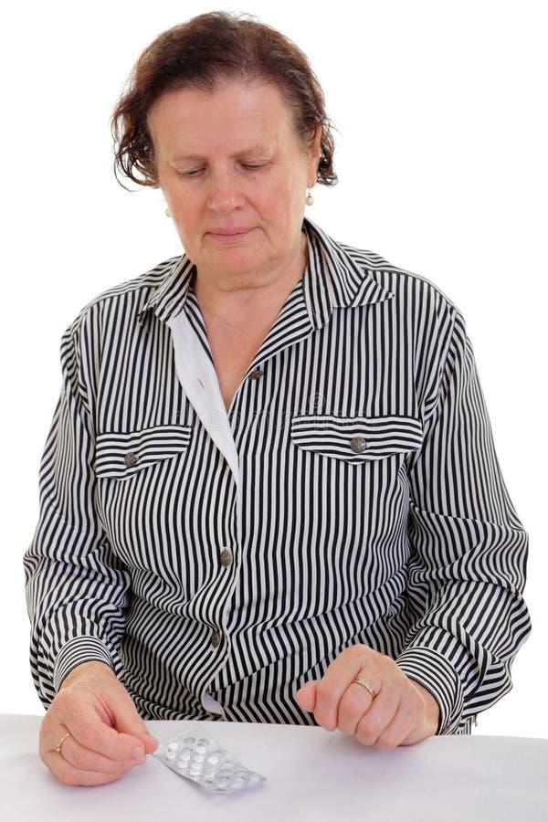 Traurige ältere Frau mit der Medizin lizenzfreie stockfotos