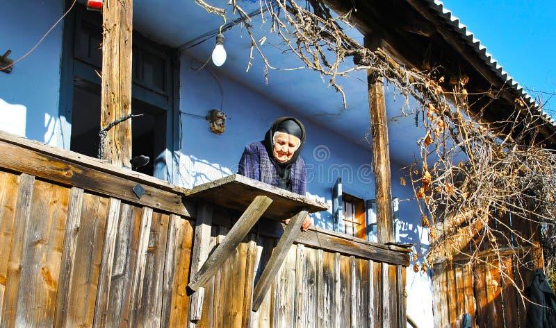 Traurige alte Dame auf ihrem traditionellen Portal stockfoto