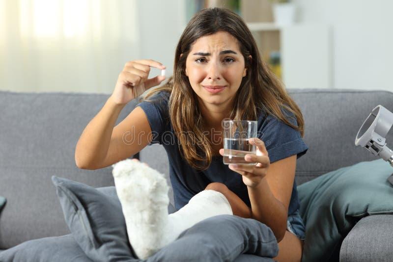 Traurige behinderte Frau, die eine Pille leidet und zeigt stockbilder