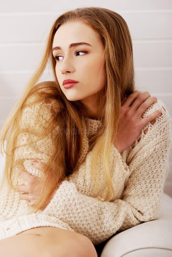 Traurige, besorgte schöne kaukasische Frau, die in der Strickjacke sitzt. lizenzfreie stockbilder