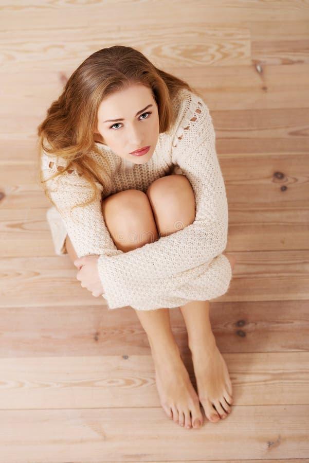 Traurige, besorgte schöne kaukasische Frau, die in der Strickjacke sitzt. lizenzfreie stockfotografie