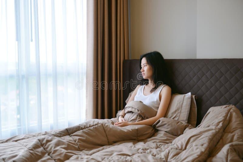 Traurige deprimierte Frau, die auf Bett im Luxusschlafzimmer denkt stockbilder
