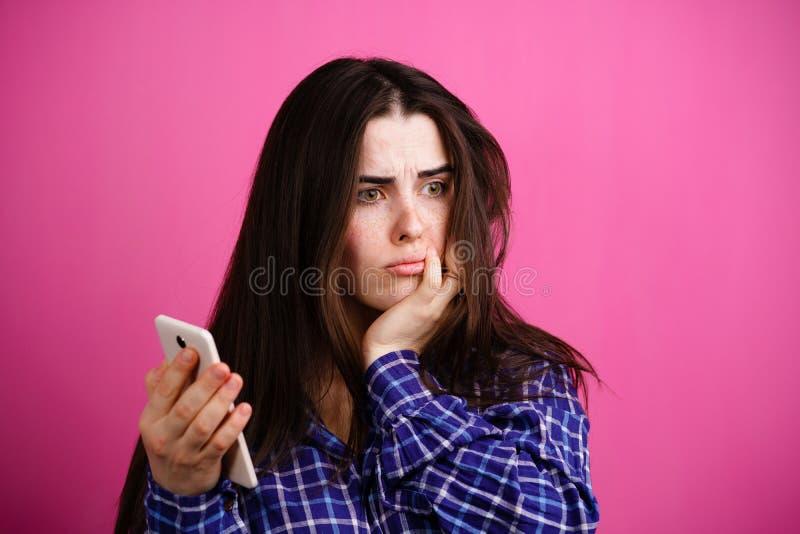 Traurige deprimierte Frau, die Handy betrachtet stockbilder