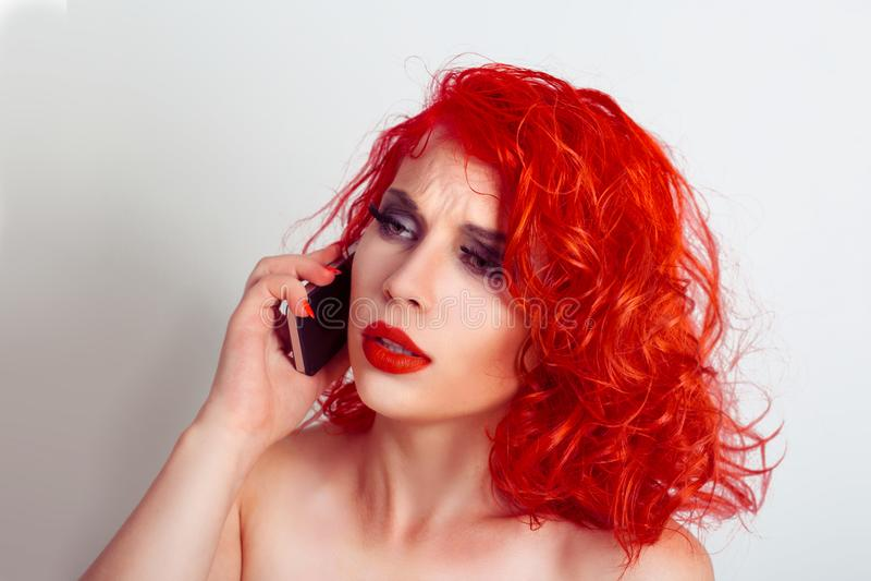 Traurige des Nahaufnahmeporträts umgekippte, skeptische, unglückliche, ernste Frau, die am Telefon spricht stockfotos