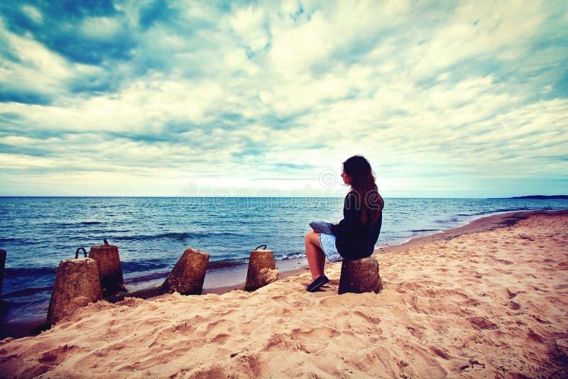 Traurige, einsame Frau, die auf dem Strand sitzt stockfotografie