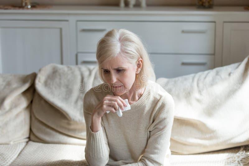 Traurige einsame mittlere Greisin, die Taschentuch, grievi halten schreit stockfoto