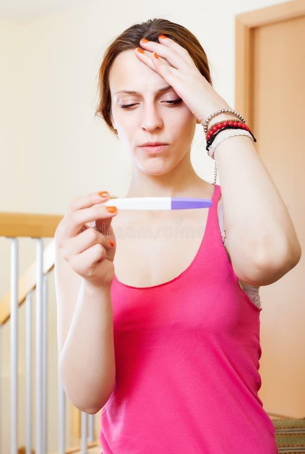 Traurige ernste junge Frau mit Schwangerschaftstest stockfotos