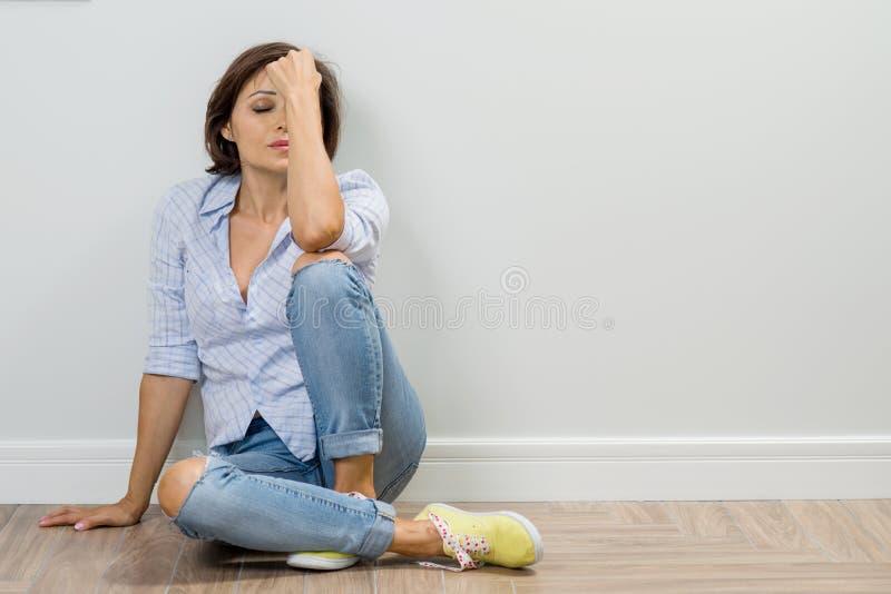 Traurige erwachsene Frau in der Krise sitzt auf dem Boden des Hauses, geschlossen ihre Augen, hält ihren Kopf in ihrer Hand lizenzfreie stockfotos