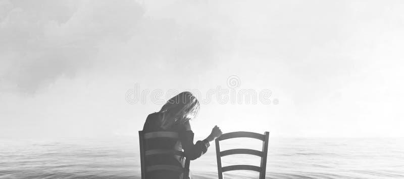 Traurige Frau betrachtet nostalgisch ihrem Liebhaber ` s leeren Stuhl lizenzfreie stockbilder