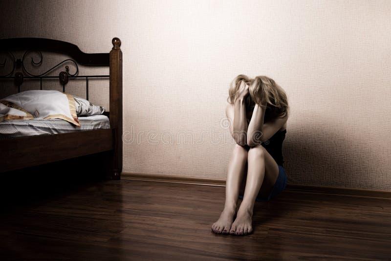 Traurige Frau, die allein in einem leeren Raum nahe bei dem Bett sitzt Häusliche Gewalt stockbild
