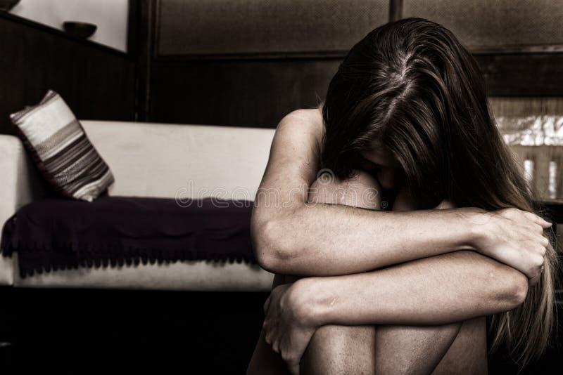 Traurige Frau, die allein in einem leeren Raum nahe bei dem Bett sitzt Häusliche Gewalt lizenzfreies stockbild