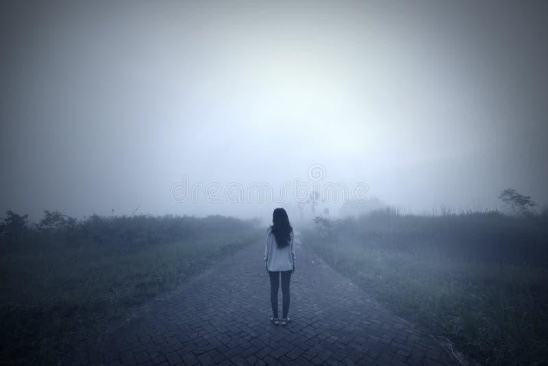 Traurige Frau, die allein an einem nebelhaften Morgen steht stockbilder