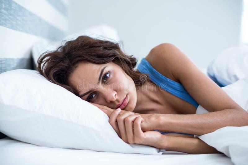 Traurige Frau, die auf Bett liegt lizenzfreies stockfoto