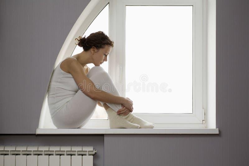 Traurige Frau, die auf Fensterbrett sitzt lizenzfreie stockfotografie