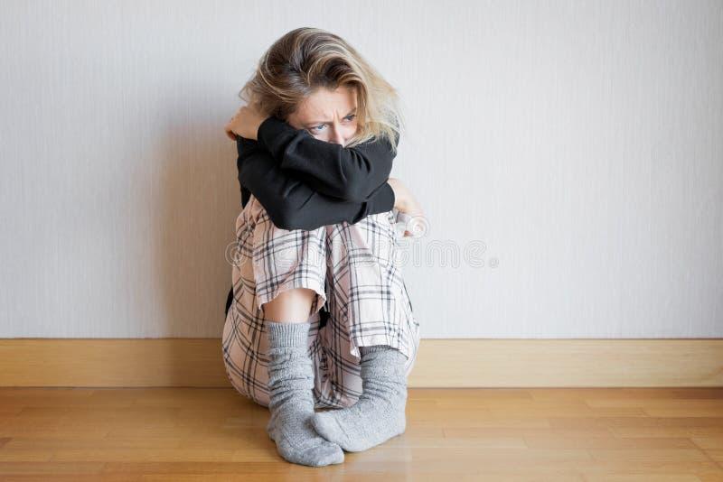 Traurige Frau, die auf Fußboden sitzt lizenzfreies stockbild