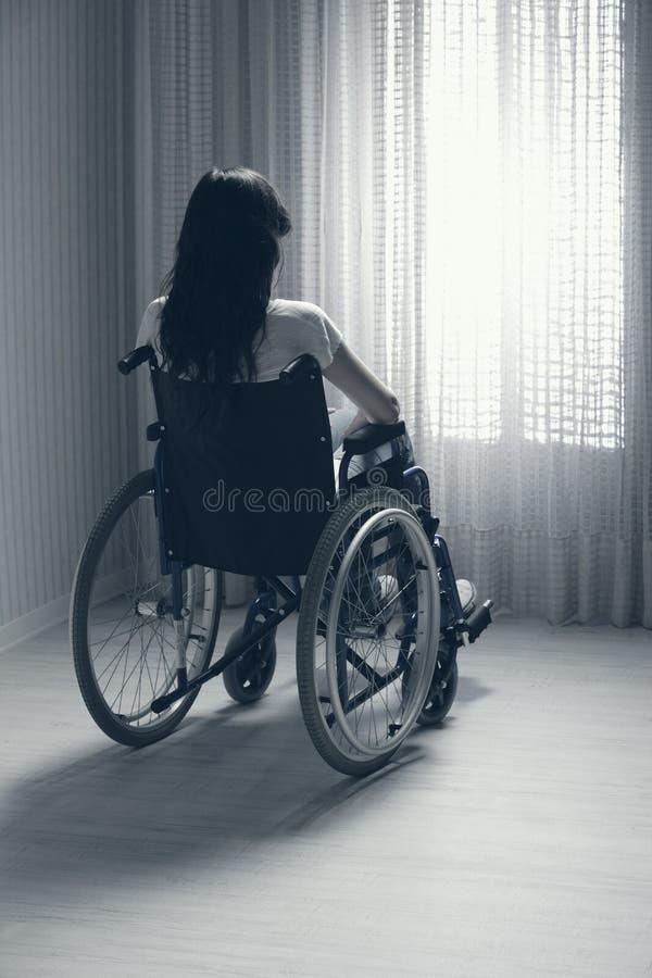 Traurige Frau, die auf Rollstuhl sitzt stockfotos