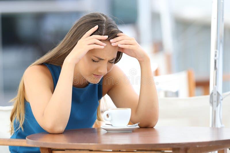 Traurige Frau, die in einer Kaffeestube sich beschwert stockbild