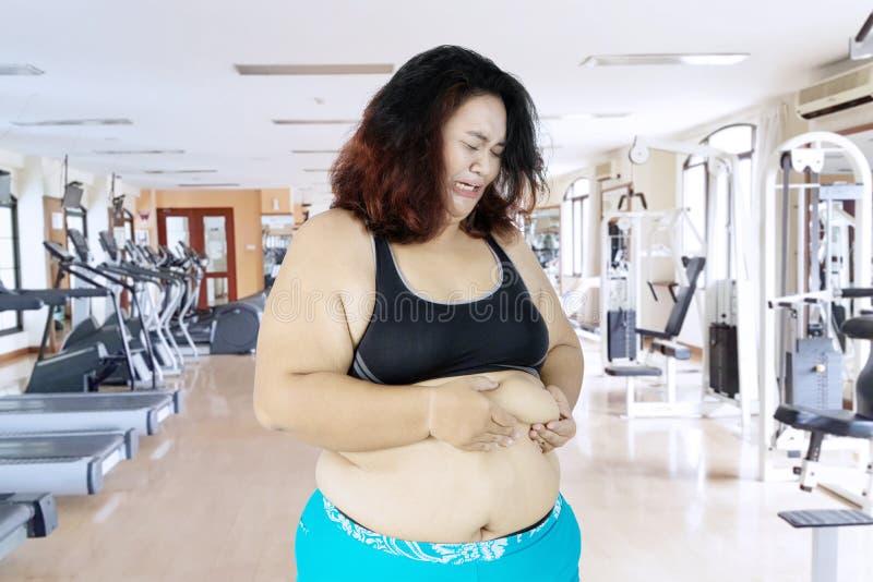Traurige Frau, die ihren Bauch fett in der Turnhallenmitte klemmt lizenzfreie stockfotografie