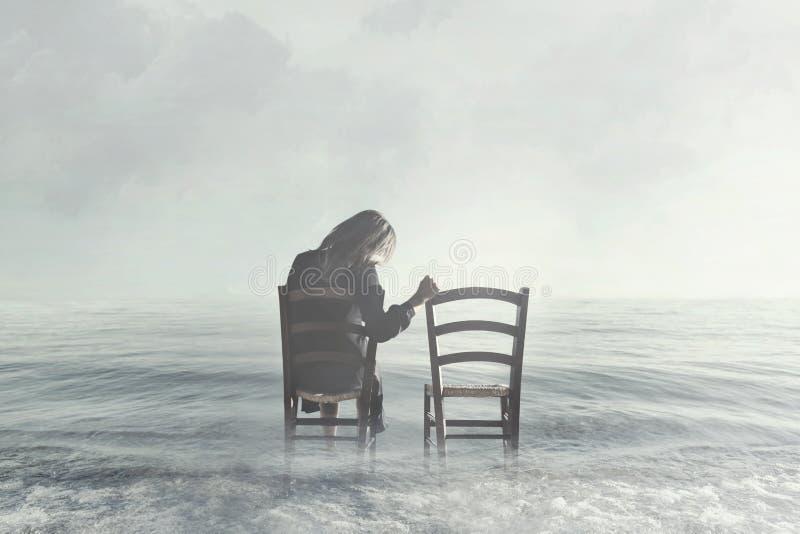 Traurige Frau, die nostalgisch ihrem Liebhaber ` s leeren Stuhl betrachtet stockfoto