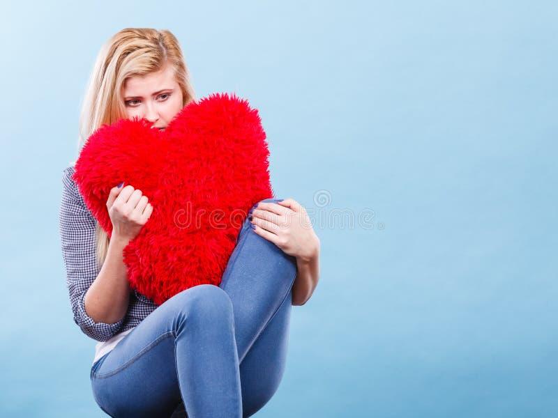 Traurige Frau, die rotes Kissen in der Herzform h?lt lizenzfreie stockbilder