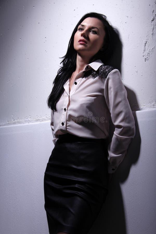 Traurige Frau die schöne junge Frau ist vor dem hintergrund einer Wand stockfotografie