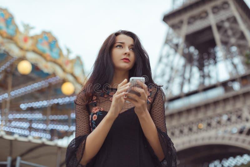 Traurige Frau, die Smartphone nahe dem Eiffelturm und dem Karussell, Paris verwendet stockfoto