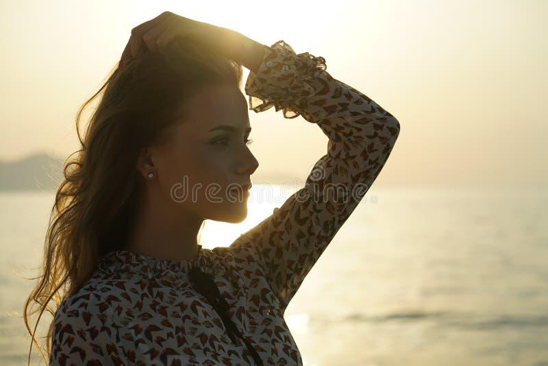 Traurige Frau durch den Sonnenuntergang lizenzfreie stockfotografie