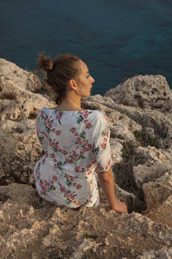 Traurige Frau durch Sonnenuntergang lizenzfreies stockfoto