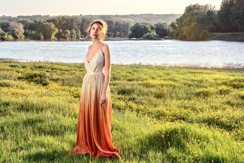 Traurige Frau in einem langen bezaubernden Kleid bei Sonnenuntergang Blick-Traurigkeitsaugen des Mädchens reizende Schöne Landsch lizenzfreie stockbilder