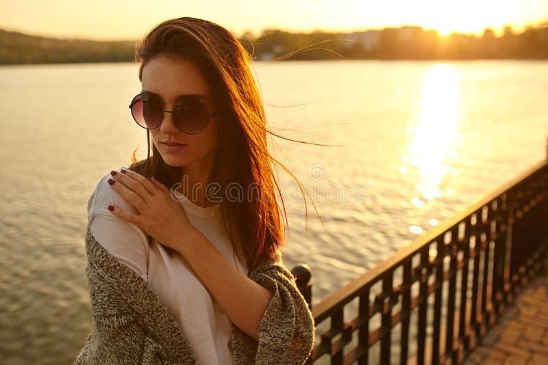 Traurige Frau gesorgt auf Sonnenunterganghintergrund stockbild