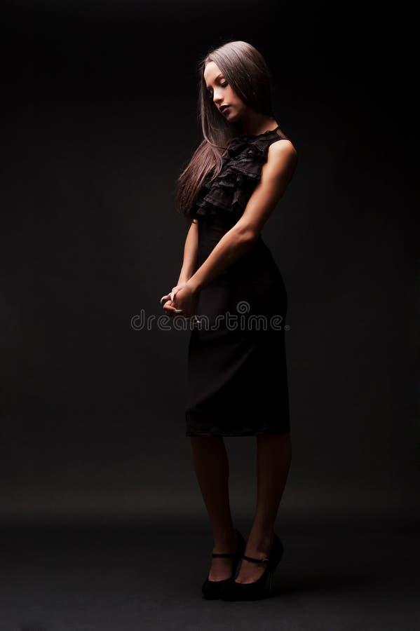 Traurige Frau im schwarzen Kleid, das unten schaut stockfotos