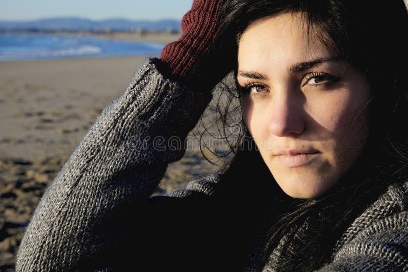 Traurige Frau im Winter auf dem Strand, der Kamera schaut lizenzfreie stockfotos