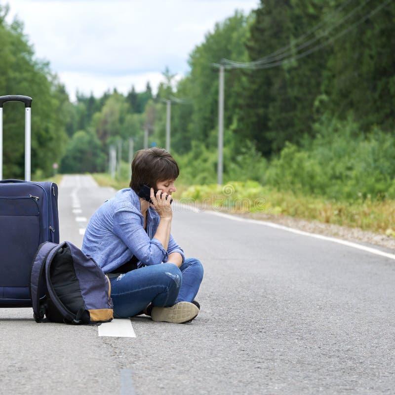 Traurige Frau mit einem Gepäck sitzt mitten in einer Asphaltstraße und dem Ersuchen um das Telefon stockbild