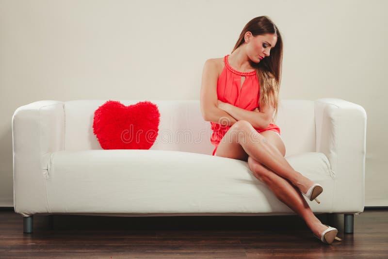 Traurige Frau mit Herzformkissen Rote Rose lizenzfreie stockbilder