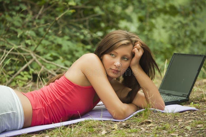 Traurige Frau mit Laptop im Wald stockfotografie