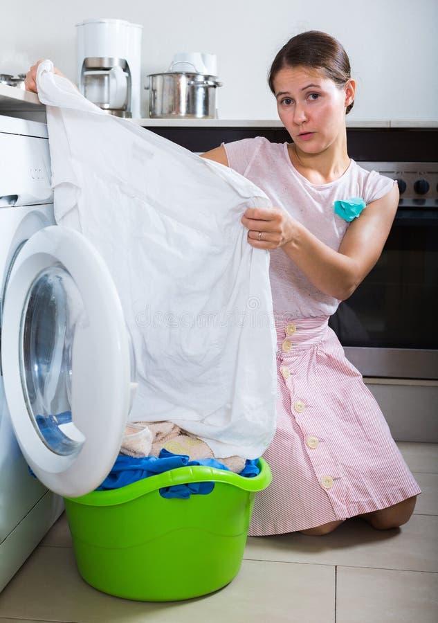 Traurige Frau nahe Waschmaschine stockfoto