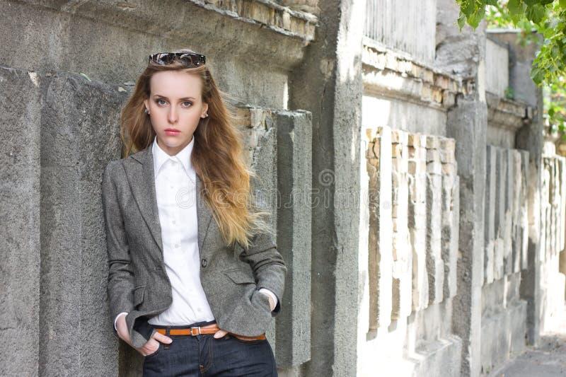 Traurige Frau steht nahe der Wand lizenzfreies stockfoto