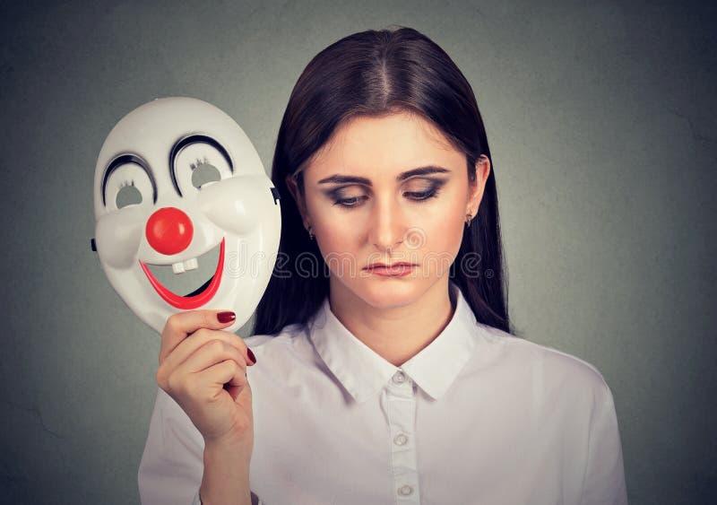Traurige Frau, welche die Clownmaske ausdrückt Glück entfernt stockfoto