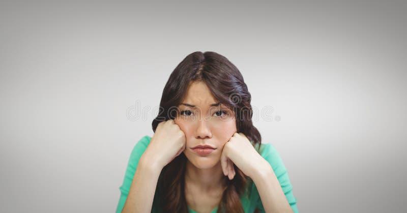 Traurige Geschäftsfrau, die ihren Kopf in ihren Händen gegen grauen Hintergrund stillsteht lizenzfreie stockfotografie