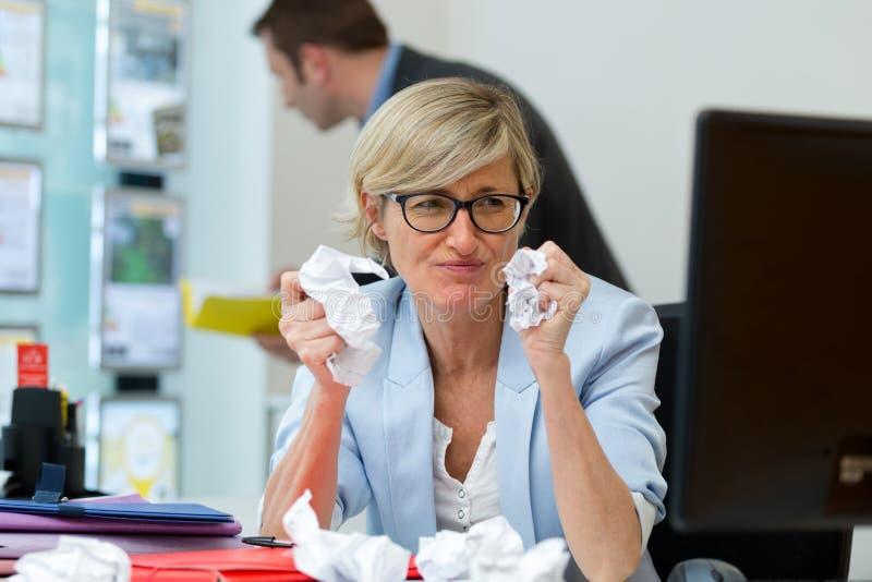 Traurige Geschäftsfrau, die am Schreibtisch sitzt lizenzfreies stockbild