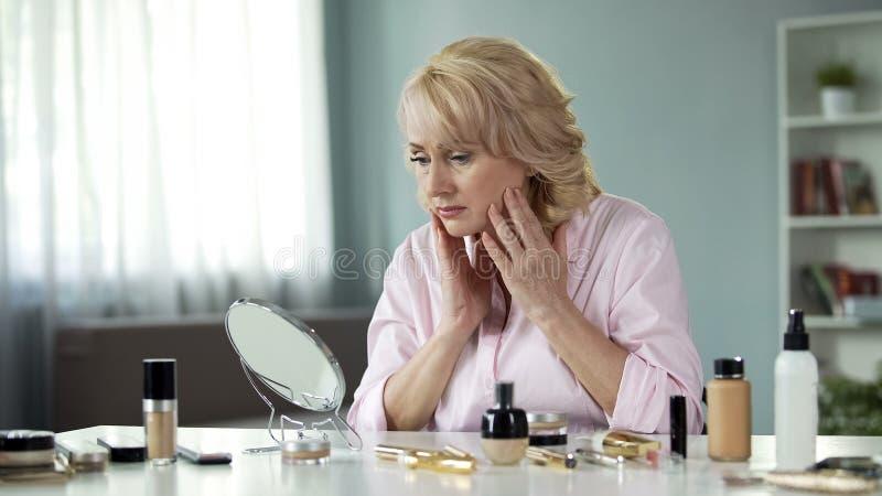 Traurige hübsche Dame, die im Spiegel, ihr Gesicht berührend, Antifaltenhautpflege schaut stockbild