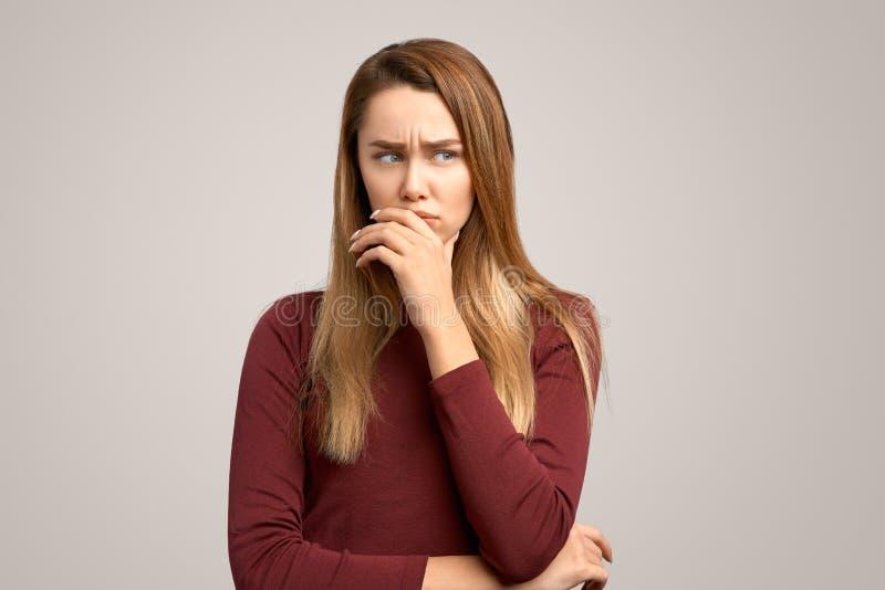 Traurige hübsche Frau mit düsterem missmutigem Ausdruck, bedeckt Mund mit der Hand Naher hoher Porträtstudent, der an Problem den lizenzfreies stockbild