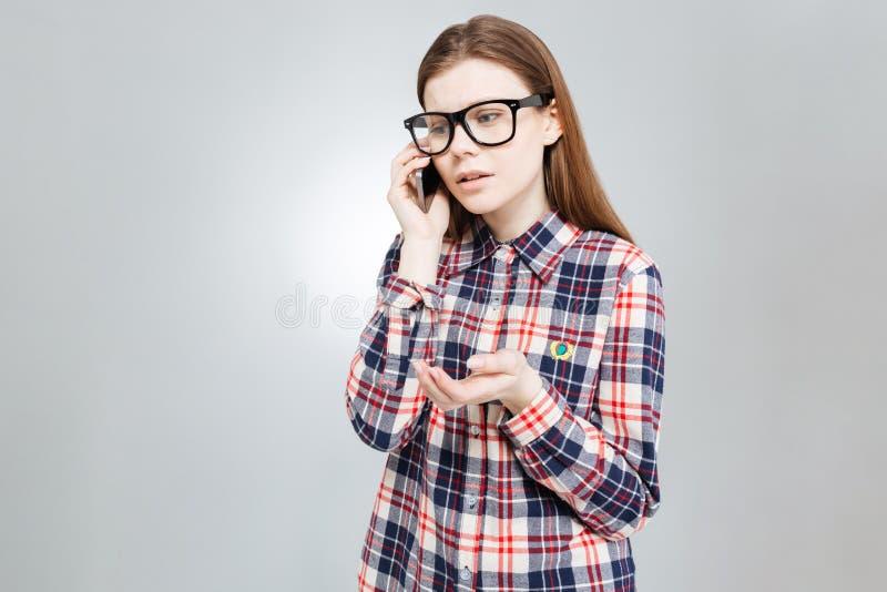 Traurige hübsche Jugendliche, die am Handy steht und spricht stockfotografie
