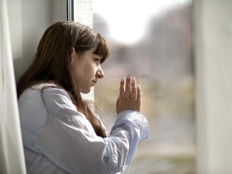 Traurige junge brunette Frau schaut heraus das Fenster stockfoto