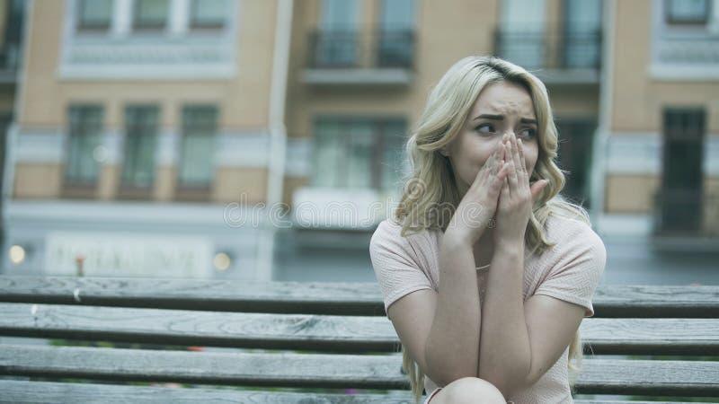Traurige junge Dame, die allein sitzen und bitterlich schreien, Verhältnis oder Gesundheitsproblem stockfotografie