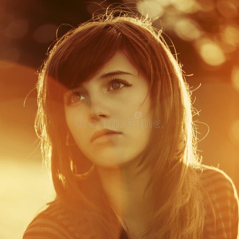 Traurige junge Frau durch Sonnenunterganglicht stockfoto