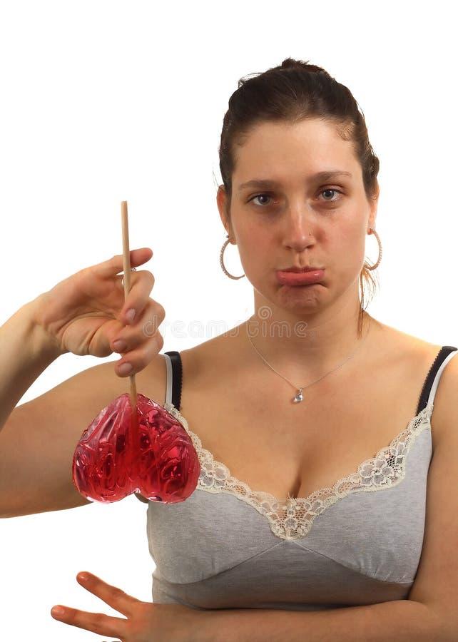Traurige junge Frau hält Inneres geformten Lutscher an stockfotografie