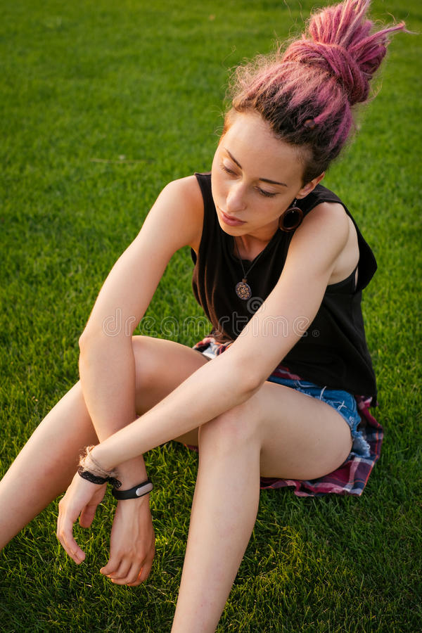 Traurige junge Frau mit den Dreadlocks, die aus den Grund sitzen lizenzfreie stockfotografie