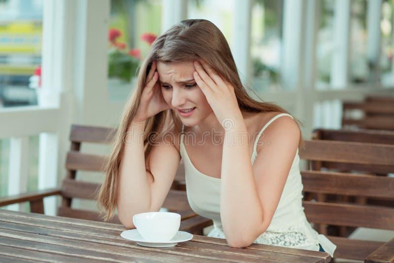 Traurige junge Frau mit Kaffeetasse in einem trendigen Café stockfoto